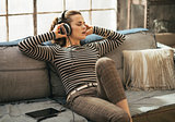 Young woman listening music in headphones in loft apartment