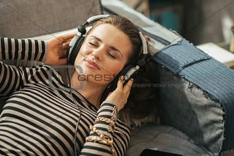 Portrait of young woman listening music in headphones while layi