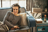 Happy young woman listening music in headphones while laying on