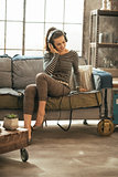 Young woman sitting on couch and listening music in headphones