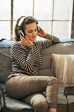 Happy young woman sitting on couch and listening music in headph