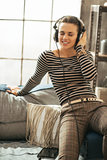 Portrait of young woman listening music in headphones in loft ap