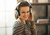 Portrait of happy young woman listening music in headphones in l