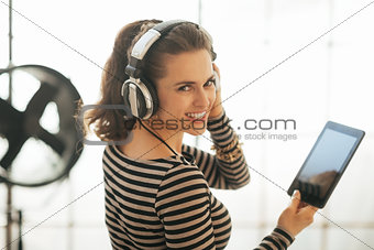 Portrait of happy young woman with tablet pc listening music in