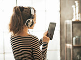 Young woman listening music in headphones in loft apartment. rea