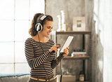 Happy young woman listening music in headphones in loft apartmen