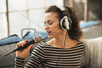 Portrait of young woman singing with microphone in loft apartmen