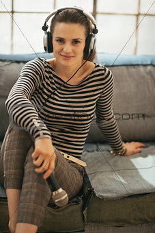 Portrait of young woman with headphones and microphone in loft a