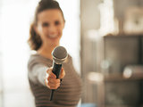 Closeup on young woman stretching microphone in camera
