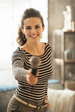 Happy young woman stretching microphone in camera
