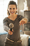 Happy young woman stretching microphone in camera and pointing