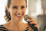 Portrait of happy young woman singing with microphone