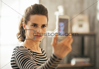 Portrait of young woman taking self photo in loft apartment
