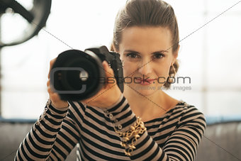 Portrait of young woman with modern dslr photo camera