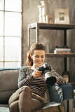 Happy young woman sitting on divan and using modern dslr photo c