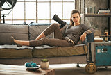Happy young woman laying on couch in loft apartment with modern