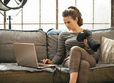 Young woman with modern dslr photo camera using laptop in loft a