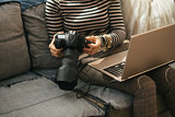 Closeup on young woman with laptop using modern dslr photo camer