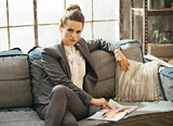 Business woman sitting on sofa in loft apartment and looking mag