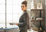 Business woman with magazine standing in loft apartment