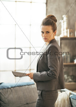 Portrait of business woman with magazine standing in loft apartm