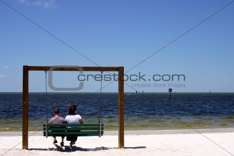 A couple sitting on a swing at the beach