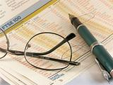 Pen and glasses on financial newspaper