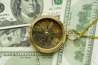 Old style gold compass with chain on dollar background