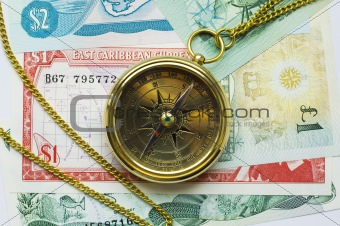Old style gold compass with chain on money background