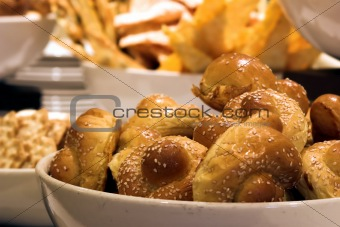 Breakfast rolls in a bowl against a backdrop of breads and breadsticks. Shallow DOF