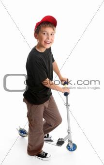 Boy standing beside a scooter