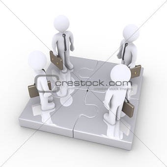 Four businessmen stand together on puzzle pieces