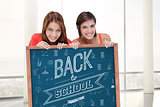 Composite image of teenage girls smiling while holding a blank poster and hiding behind it
