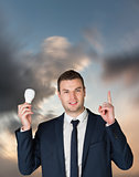 Composite image of businessman holding light bulb and pointing