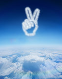 Composite image of cloud in shape of hand making peace sign