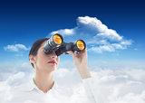 Composite image of business woman looking through binoculars