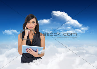 Composite image of thoughtful elegant brown haired model holding tablet