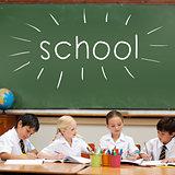 School against cute pupils sitting at desk