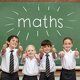 Maths against cute pupils showing thumbs up in classroom