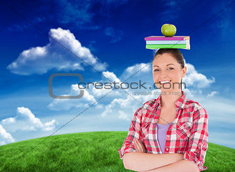 Composite image of pretty student holding an apple and books on her head