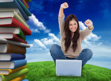 Composite image of woman looks straight ahead as she celebrates in front of her laptop