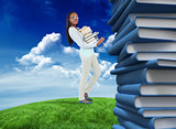 Composite image of side view of young woman carrying a pile of books