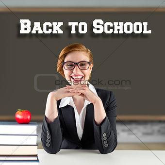 Composite image of redhead teacher sitting at desk