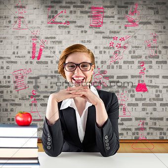 Composite image of redhead teacher sitting at desk