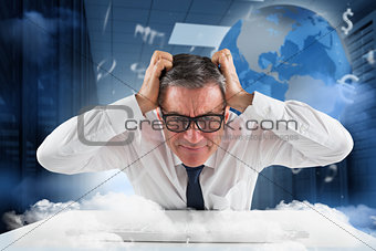 Composite image of stressed businessman using a keyboard