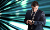Composite image of handsome businessman checking the time