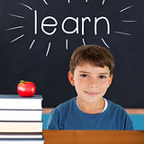 Learn against red apple on pile of books in classroom