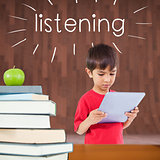 Listening against red apple on pile of books