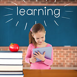 Learning against red apple on pile of books in classroom