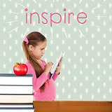 Inspire against red apple on pile of books